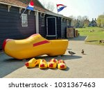 Small photo of Giant clog lined up outside workman's house, with four smaller clogs