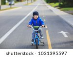 happy boy on a bicycle at... | Shutterstock . vector #1031395597