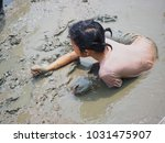 kid play mud at mangrove forest | Shutterstock . vector #1031475907