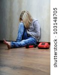 Young woman sitting on a wooden floor with old phone. - stock photo