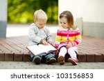 Cute Boy And Girl Reading A Book