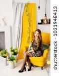 an elegant woman sitting on a... | Shutterstock . vector #1031948413