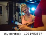 smiling personal trainer using... | Shutterstock . vector #1031953597
