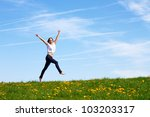 smiling young girl jumping against blue sky - stock photo