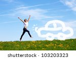 smiling young girl jumping against blue sky is pleased about her first car - stock photo