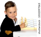 little boy is playing chess on... | Shutterstock . vector #1032097063