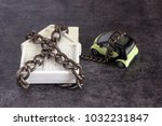 Small photo of Small white house, car and a decorative chain on a dark background. Concept - risks, lose property, seize, mortgage.