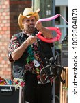Small photo of Alpharetta, GA/USA - September 30, 2017: A man uses an air pump to blow up a balloon as he makes balloon animals at the Scarecrow Harvest fall festival on September 30, 2017 in Alpharetta, GA.