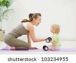 Baby helping mother lifting dumb-bells - stock photo