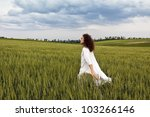 Young white dressed adult is striding through field of cereal plant and let flow his thoughts. - stock photo