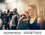 Small photo of Fit young woman holding a dumbell while working out with other people during an exercise class at a gym