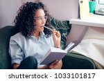 Small photo of side view shot of woman having pencil on mouth and holding book indoors. bookworm. broaden mind. best friend getting useful information