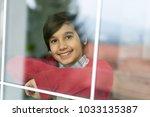 happy boy behind window glass | Shutterstock . vector #1033135387