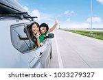 happy siblings waving hands... | Shutterstock . vector #1033279327