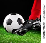 soccer ball and feet on the football field - stock photo