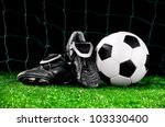 soccer ball and cleats on the football field - stock photo