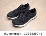 black sneakers on wooden... | Shutterstock . vector #1033325743