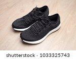black sneakers on wooden... | Shutterstock . vector #1033325743