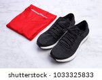 black sneakers and folded red... | Shutterstock . vector #1033325833