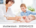 Small photo of Mother and son bathe newborn baby in the bath in the bath