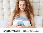 Small photo of Attractive concentrated female with curly hair checks mail on smart phone, uses modern application, spends free time in comfortable bed, plans or thinks how spend weekends. Woman messages online