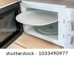 an open microwave with a white... | Shutterstock . vector #1033490977