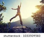 hipster woman hiker jumping on... | Shutterstock . vector #1033509583