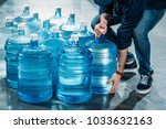 man delivering large bottles... | Shutterstock . vector #1033632163