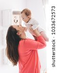 young woman lifting her baby... | Shutterstock . vector #1033672573