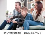 excited family playing video... | Shutterstock . vector #1033687477