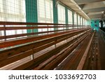 rows of empty wooden benches in ... | Shutterstock . vector #1033692703