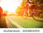 a woman is cycling into the... | Shutterstock . vector #1033841053