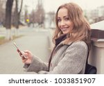 young pretty woman in coat... | Shutterstock . vector #1033851907