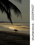 A man carrying his surfboard to the beach for early morning waves - stock photo