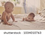 two funny siblings on the bed... | Shutterstock . vector #1034010763