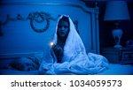girl sitting in dark bedroom... | Shutterstock . vector #1034059573