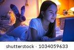 smiling girl in pajamas typing... | Shutterstock . vector #1034059633