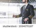 Small photo of Cropped image of handsome young male pilot in the airport terminal.