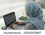 young muslim girl wotking on... | Shutterstock . vector #1034093887