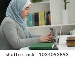 young muslim girl wotking on... | Shutterstock . vector #1034093893