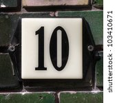 enameled plate with the house number ten, attached to a wall of green bricks. - stock photo