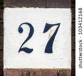 hand painted house number twenty seven on a white painted square. - stock photo