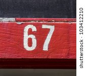 house number sixty-seven, on a red painted door post - stock photo