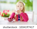 pretty little girl eating... | Shutterstock . vector #1034197417