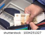 Small photo of Repayment credit. hands Men with Russian 100 rubles from wallet. Using atm bank machine. withdraw money at cash points