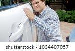 portrait of young man gently... | Shutterstock . vector #1034407057