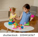 two little girls play with... | Shutterstock . vector #1034416567