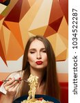 Small photo of Portrait of attractive long haired woman with slightly ajar mouth and red lips eating Italian pasta with seafood and vegetables. Gorgeous young female model posing with delicious fettuccine on fork.