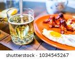 Small photo of Closeup of large breakfast brunch plate with fried eggs, hash browns shredded potatoes, sausage tako octopus, collagen yellow drink with spoon