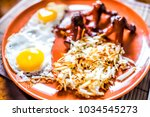 Small photo of Closeup of large breakfast brunch plate with fried eggs, hash browns shredded potatoes, sausage tako octopus
